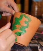 L painting a Christmas tree on one of her pots.
