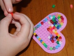 A placing beads on her peg board.