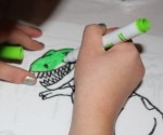 L colouring her dinosaur.