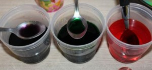 A's cups of purple, green and orange water.