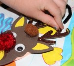 Placing tiny bells on the reindeer's antlers.